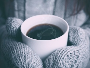 Mittens around a warming cup of coffee with enhance coaching