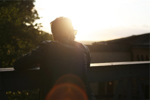 Person looks toward the sun and uses enhance coaching to look to the future and improve performance and self development
