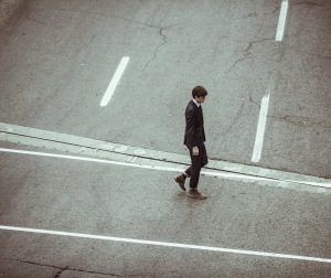 Man crosses the road after help from enhance coaching to take control, be successful and move career forward